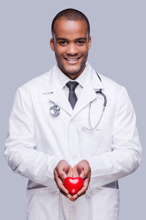Your heart in right hands. Confident African doctor holding heart shape toy and smiling while standing against grey background