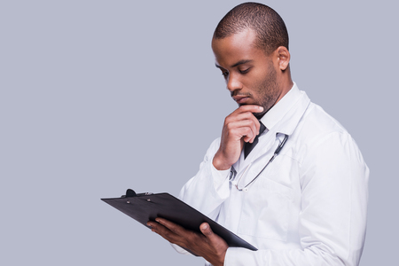 Thinking about proper medication. Thoughtful African doctor holding clipboard and looking at it while standing against grey background
