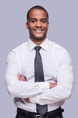 Young and successful. Confident young African man in shirt and tie keeping arms crossed and smiling while standing against grey background