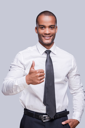 Thumb up for success! Confident young African man in shirt and tie showing his thumb up and smiling while standing against grey background  photo
