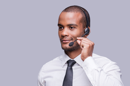 Providing best support. Confident young African man adjusting his headset and looking away while standing against grey background  photo