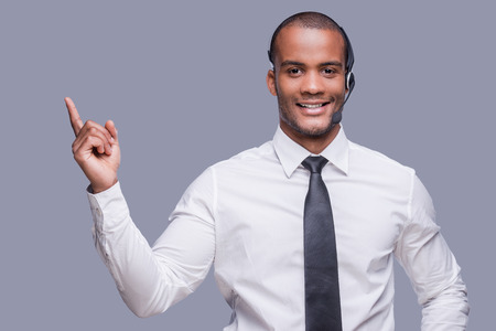 Your text here. Confident young African man in headset pointing away and smiling while standing against grey background  photo