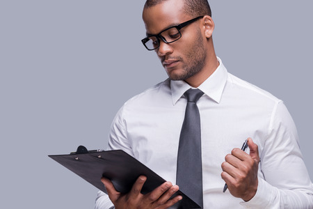 writing pad: Reading document before signing. Confident young African man in shirt and tie keeping arms crossed and smiling while standing against grey background  Stock Photo