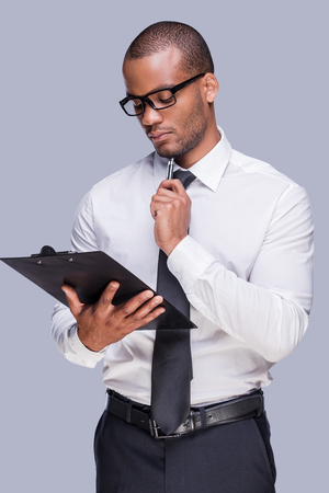Examining contract before signing. Thoughtful young African man in shirt and tie holding clipboard and touching his chin with pen while standing against grey background  photo