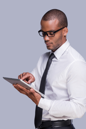 Examining his new gadget. Confident young African man in shirt and tie working on digital tablet while standing against grey background