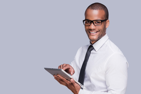 Businessman with digital tablet. Confident young African man in shirt and tie working on digital tablet and smiling while standing against grey background  Stok Fotoğraf