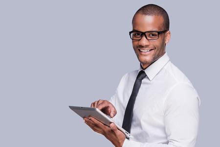 hombres negros: Hombre de negocios con la tableta digital. Hombre africano joven confidente en camisa y corbata trabaja en la tablilla digital y sonriendo mientras está de pie contra el fondo gris Foto de archivo