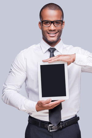 Copy space on his digital tablet. Confident young African man in shirt and tie showing his digital tablet and smiling while standing against grey background  photo