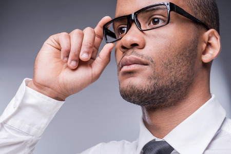 beauty shot: Confident businessman. Low angle view of thoughtful young African man in shirt and tie adjusting his eyeglasses and looking away while standing against grey background  Stock Photo