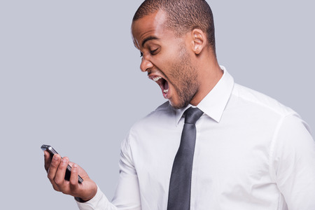 Very bad news. Furious young African man in shirt and tie holding mobile phone and shouting while standing against grey background  photo