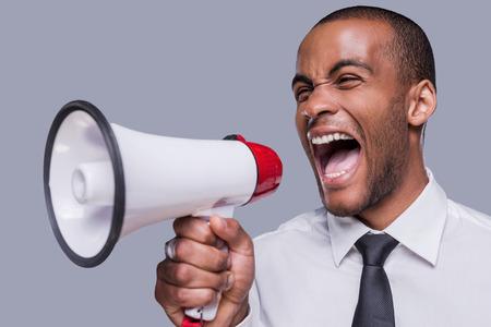 you can: ¿Puedes oírme ahora? Hombre africano joven furioso en formalwear grita en el megáfono mientras está de pie contra el fondo gris