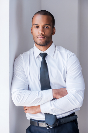 Successful businessman. Handsome young African man in shirt and tie looking at camera and keeping arms crossed while leaning at the wall