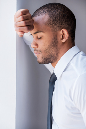 Tired and overworked. Side view of depressed young man in shirt and tie leaning at the wall and keeping eyes closed photo