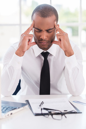 tired worker: Stressed and tired. Depressed young African man in formalwear holding head in hands and keeping eyes closed while sitting at his working place