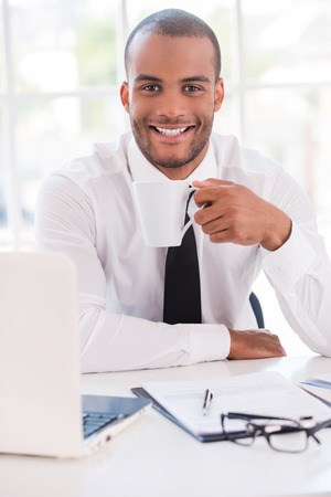 Coffee break. Handsome young man in shirt and tie drinking coffee and smiling while sitting at his working place photo