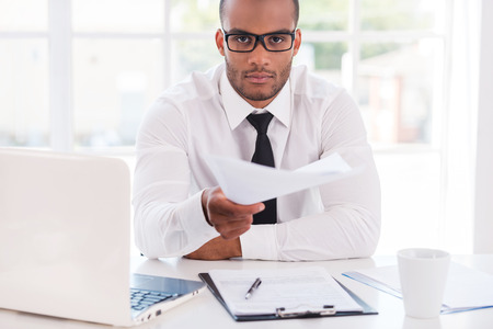 I have some paperwork for you! Confident young African man in shirt and tie stretching out documents and looking at you while sitting at his working place photo