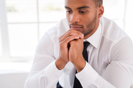 african ethnicity: Lost in thoughts. Thoughtful young African man in shirt and tie holding hands on chin and looking away while sitting at his working place