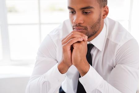 personas pensando: Perdido en pensamientos. Hombre africano joven pensativo en camisa y corbata de la mano en la barbilla y mirando a otro lado mientras se est� sentado en su lugar de trabajo Foto de archivo