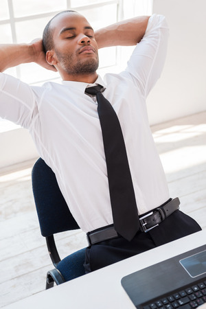 Total relaxation. Relaxed young African man in shirt and tie holding hands behind head while sitting at his working place photo
