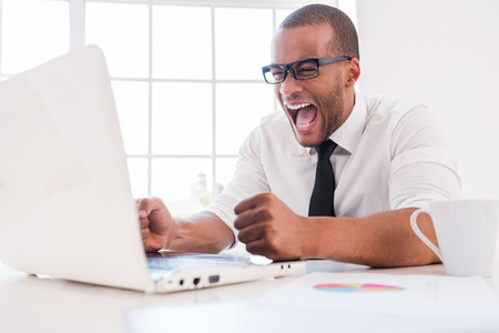 business failure: Too stressful work. Furious young African man in shirt and tie shouting while looking at laptop while sitting at his working place Stock Photo