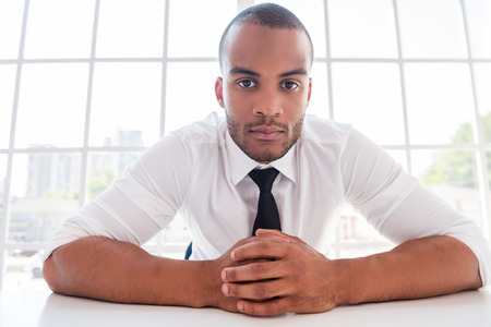 you can: Le puedo ayudar en algo? Hombre africano joven confidente en camisa y corbata con las manos juntas y mirando a la cámara mientras estaba sentado en su lugar de trabajo