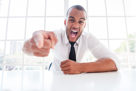 Furious boss. Furious young African man in shirt and tie pointing you and shouting while sitting at his working place photo