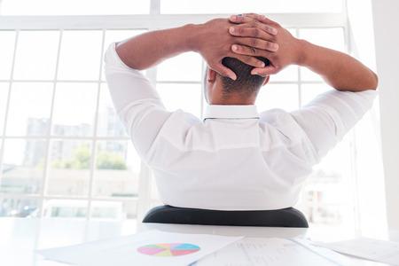 relajado: Tiempo para relajarse. Hombre africano joven relajado en camisa y corbata con las manos detr�s de la cabeza mientras estaba sentado en su lugar de trabajo