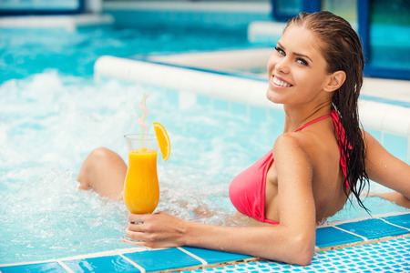 Spending great time in jacuzzi. Rear view of attractive young woman in bikini relaxing in Jacuzzi and smiling Фото со стока