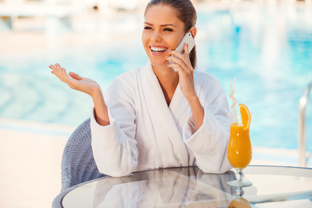Sharing good news with friends. Happy young woman in bathrobe talking on the mobile phone and gesturing while sitting at the table by the pool photo