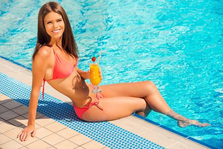 mujer desnuda sentada: Pasar junto a la piscina gran tiempo. Joven y bella mujer en bikini sentada en la piscina con un cóctel y mirando a cámara con una sonrisa