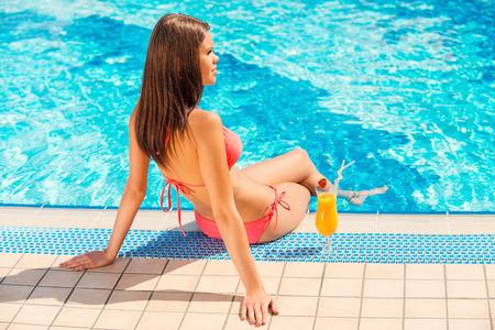 mujer desnuda sentada: Pasar tiempo junto a la piscina de verano. Vista posterior de la mujer joven en bikini sentada en la piscina con un cóctel junto a ella Foto de archivo