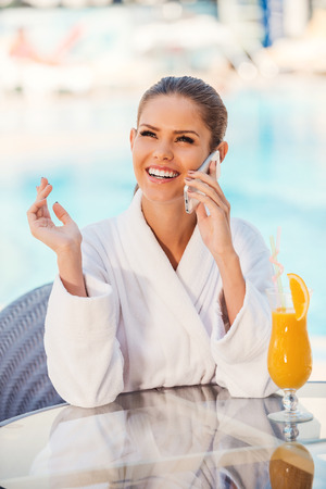 Spending great time poolside. Beautiful young woman in bathrobe talking on the mobile phone and smiling while sitting at the table by the pool photo