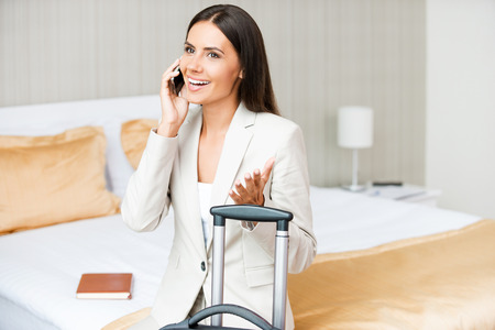 dearest: Taking time to call her dearest. Beautiful young businesswoman in suit talking on the mobile phone and smiling while sitting on the bed in hotel room  Stock Photo
