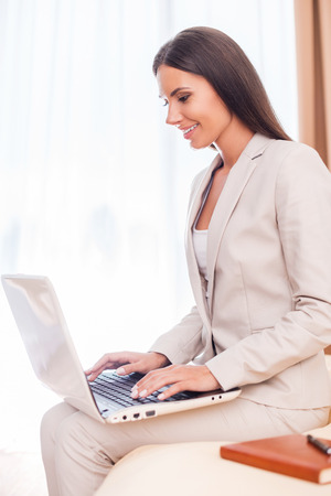 Staying connected. Side view of beautiful young businesswoman in suit working on laptop and smiling while sitting on the bed  photo