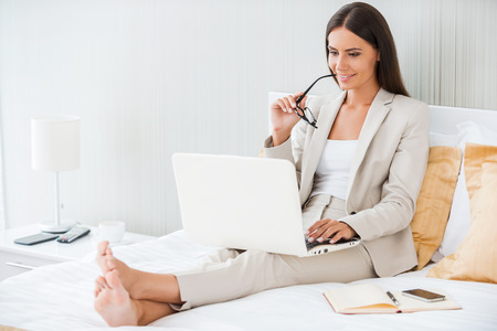 Working in hotel room. Beautiful young businesswoman in suit working on laptop and smiling while sitting in bed at the hotel room photo