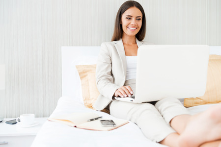 Working in hotel room. Confident young businesswoman in suit working on laptop and smiling while sitting in bed at the hotel room photo