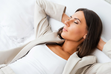 Tired after hard working day. Top view of beautiful young businesswoman in suit holding hands behind head and keeping eyes closed while lying in bed at the hotel room  photo