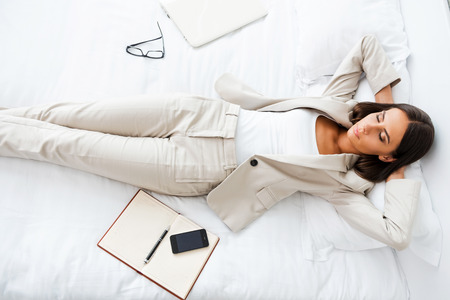 Taking rest hard working day. Top view of beautiful young businesswoman in suit holding hands behind head and keeping while lying in bed at the hotel room  Stock Photo