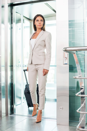 Executive on the go. Full length of beautiful young businesswoman in formalwear carrying suitcase smiling while getting out of elevator photo