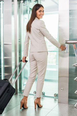Ready to new business trip. Rear view of confident young businesswoman in formalwear pushing button while standing near elevator entrance