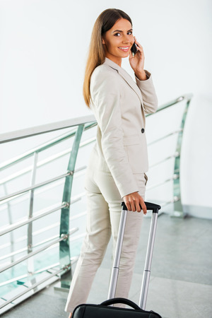 looking over shoulder: Businesswoman on the go. Beautiful young businesswoman in suit talking on the mobile phone and smiling while getting out of elevator