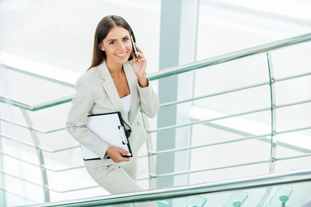 Successful businesswoman. Beautiful young businesswoman in formalwear talking on the mobile phone and smiling while moving up by staircase photo