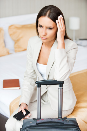 Tired of traveling. Depressed young businesswoman in formalwear holding head in hand while sitting on the bed in hotel room  photo