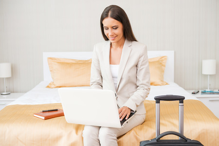 Staying connected anytime. Beautiful young businesswoman in suit working on laptop and smiling while sitting on the bed in hotel room  photo