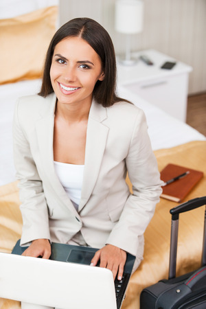 Staying in touch with my colleagues. Top view of beautiful young businesswoman in suit working on laptop and smiling while sitting on the bed in hotel room  photo