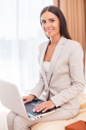 I love my job! Beautiful young businesswoman in suit working on laptop and smiling while sitting on the bed  photo