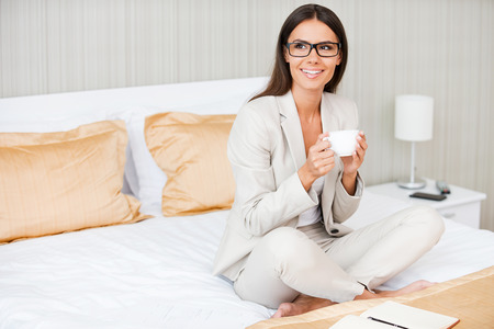 Relaxing after hard working day. Beautiful young smiling businesswoman in suit drinking coffee and looking away while sitting on the bed in hotel room