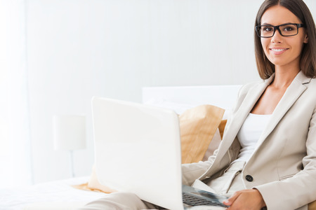 Businesswoman in hotel. Beautiful young businesswoman in suit working on laptop and smiling while sitting in bed at the hotel room photo