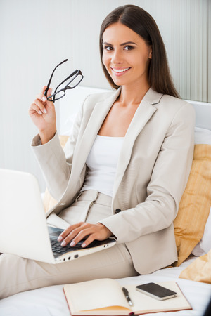staying: Staying connected anytime and everywhere. Beautiful young businesswoman in suit working on laptop and smiling while sitting in bed at the hotel room