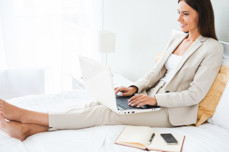 Businesswoman in hotel room. Beautiful young businesswoman in suit working on laptop and smiling while sitting in bed at the hotel room photo